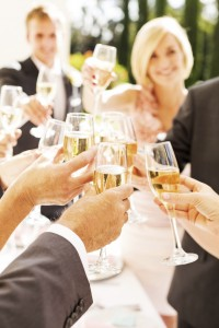 Guests And Couple Toasting Champagne Flutes During Reception